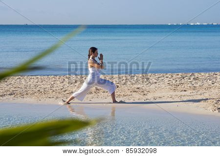 Woman practicing yoga at a tropical beach