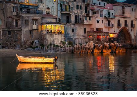 Old Boat Drifting In Cefalu Harbor At Dusk
