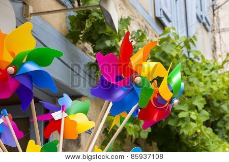 Brightly Colored Wind Toys Against An Old Wall Ang Grape Vine.
