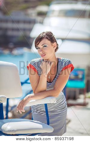 Summer portrait of attractive brunette near the yacht club.
