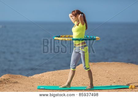 Young woman exercising with a hula Hoop,on a sandy beach.