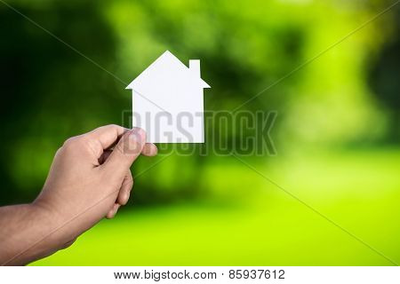 Man's hand holding a cardboard house