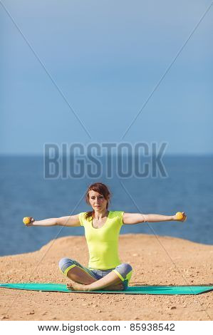 A young woman fitness trainer, shows a set of exercises with dumbbells.