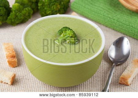Portion of vegan green broccoli cream soup with croutons and spoon