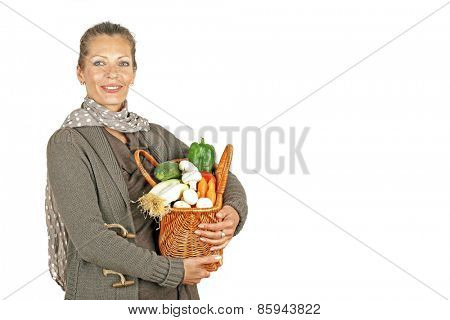 Beautiful woman with a basket full of vegetables from the market
