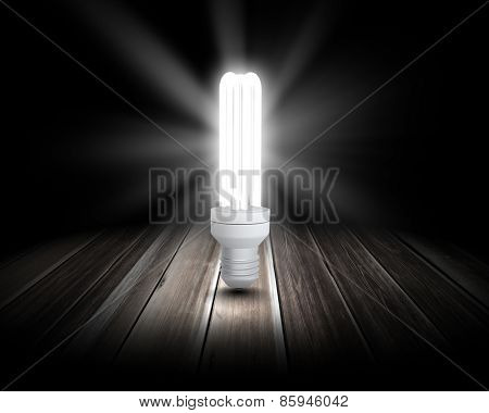 Background image with glowing light bulb on wooden surface