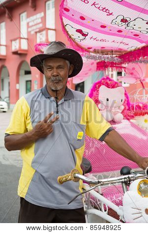 MALACCA, MALAYSIA - CIRCA JANUARY, 2015: Portrait of an unusually flamboyant Malay rickshaw man in a hat, met on the street in Malacca.