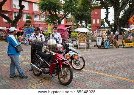 MALACCA, MALAYSIA - CIRCA JANUARY, 2015: Police with motorcycles at the Dutch Square in the historic center of Malacca. Malacca was included in the list of UNESCO World Heritage Sites in 2008.