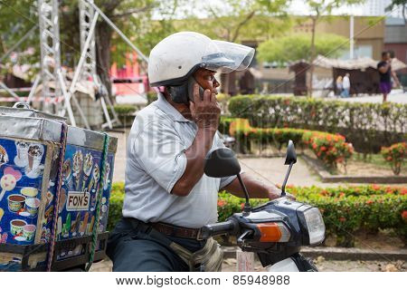 MALACCA, MALAYSIA - CIRCA JANUARY, 2015: The seller of ice cream on a motorcycle talking on a cell phone.