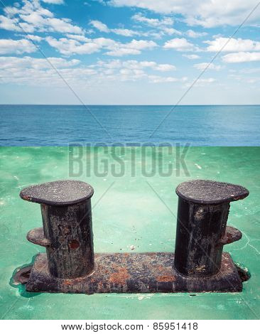Old Black Rusted Stern Bollard Mounted On Green Ship Deck