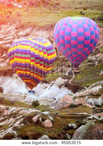 Colorful Hot Air Balloons Flying Over Rock Landscape At Cappadocia