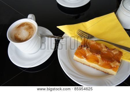 Place setting with a cup coffee and apricots cake