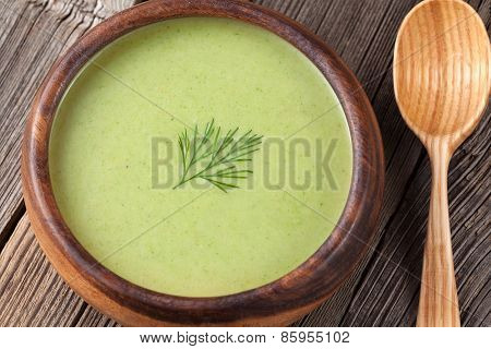 Green broccoli cream soup in a wooden bowl with spoon