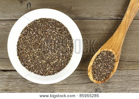Bowl of chia seeds over wood with spoon