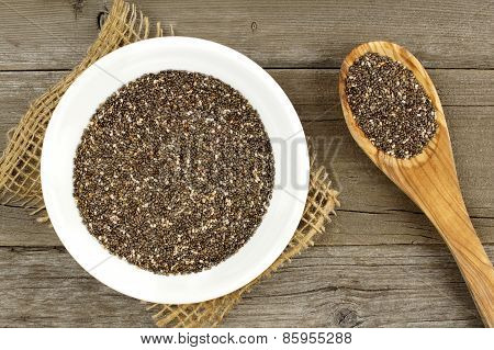 Bowl of chia seeds on wood with spoon