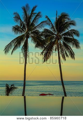 Palm trees reflected in smooth water of the pool on the beach. Delicate sunset on the popular resort island of Koh Samui