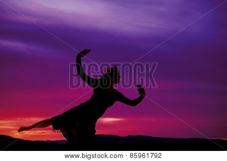 Silhouette Of A Woman In A Skirt On One Knee Arms Out
