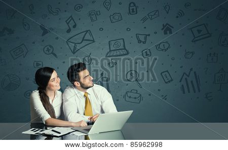Successful business couple with all kind of media icons in background