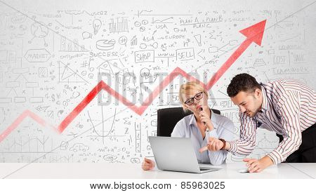 Business man and woman sitting at table with market hand drawn diagrams