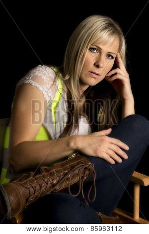 Woman Sitting In A Chair Leg Upon Black Looking