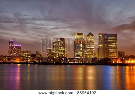 Skyline of London Canary Wharf at sunset with colorful light reflections on Thames River