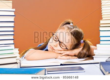 Little scholar girl with pile of books sleeping and tired