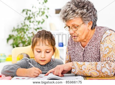 Grandmother and daughter writing and learning homework at domestic room