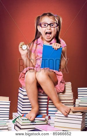 Little scholar girl with pile of books - time concept