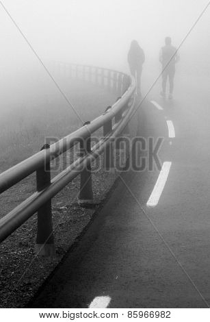 Couple Walking Along The Road In The Fog
