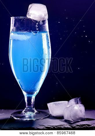 Blue drink with ice cube on black background. Cocktail card 9.