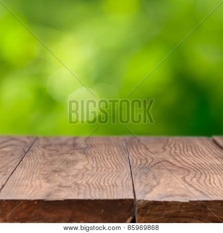 Empty wooden table against green natural background