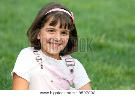Smiling Girl On The Grass
