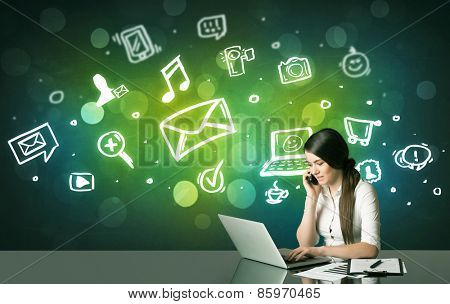 Businesswoman sitting at the black table with social media symbols on the background