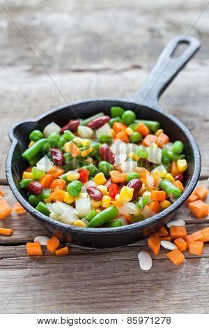 Mixed Vegetable Meal In Old Frying Pan And Ingredients On Wooden Rustic Table.