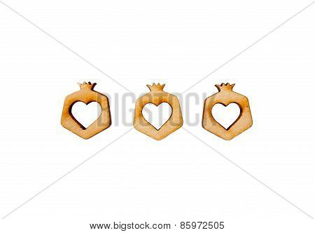 Three carved wooden pomegranate with a heart in the middle isolated on white background