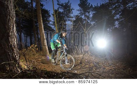 Mountain biker cycling through the woods on an off road trail at sunset. Backlit image