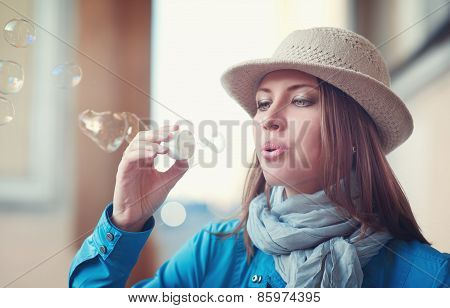 Beautiful Young Hipster Woman In Hat Blowing Bubbles
