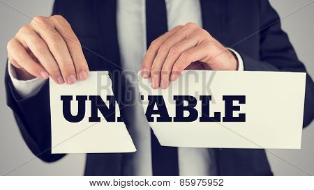 Man Holding A Torn Paper Sign In His Hands With The Words - Un - Able