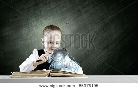 Schoolgirl examining opened book with magnifying glass