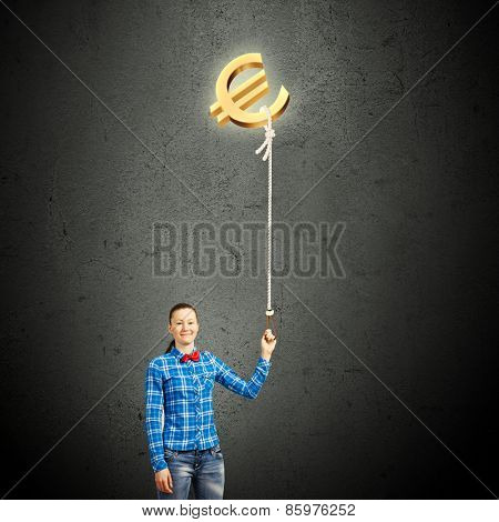 Young girl in casual holding euro symbol on rope