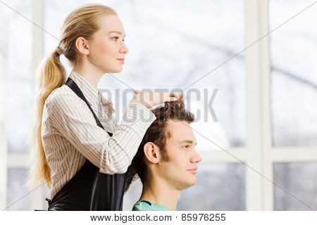 Young man in chair at barbers and woman hairdresser