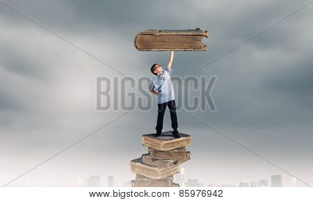 Young man holding huge book above head on one hand