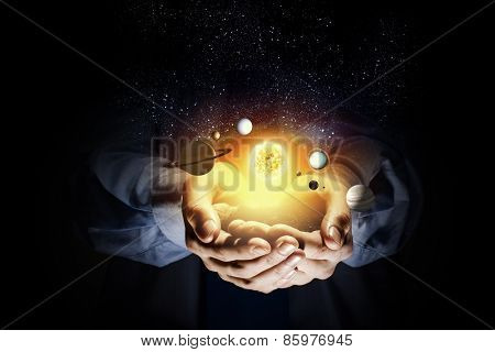 Close up of human hand with planet of sun system