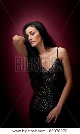 Attractive brunette woman in a black posing dramatic on purple background. Long hair female