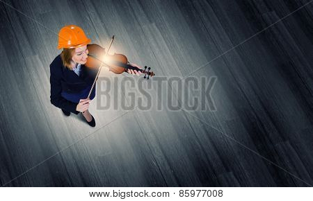 Top view of businesswoman in helmet playing violin