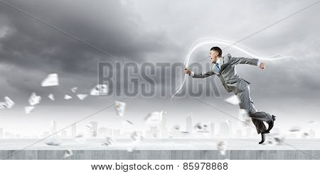 Young running businessman with colorful splashes in hand