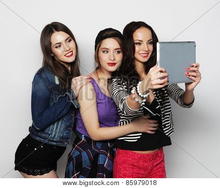 Three girls friends taking selfie with digital tablet, studio shot over gray vackground