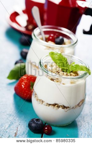 Healthy breakfast - yogurt with muesli and berries - health and diet concept. Blue background