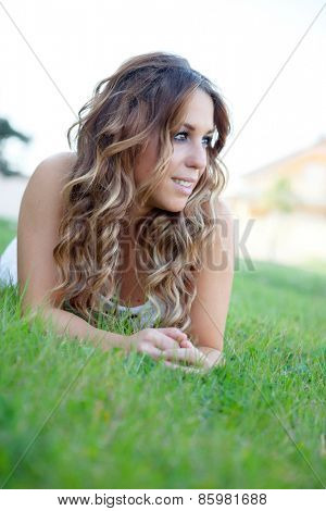 Cool pretty girl lying on the grass with a beautiful smile
