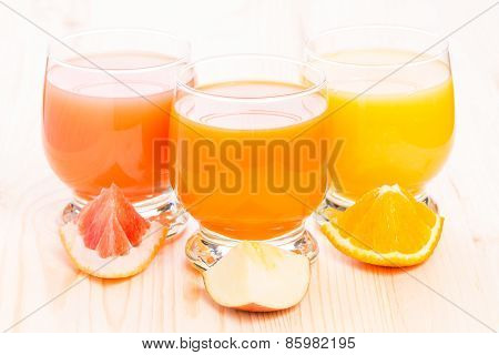 Various Fresh Juice In Glass On Wooden Table.